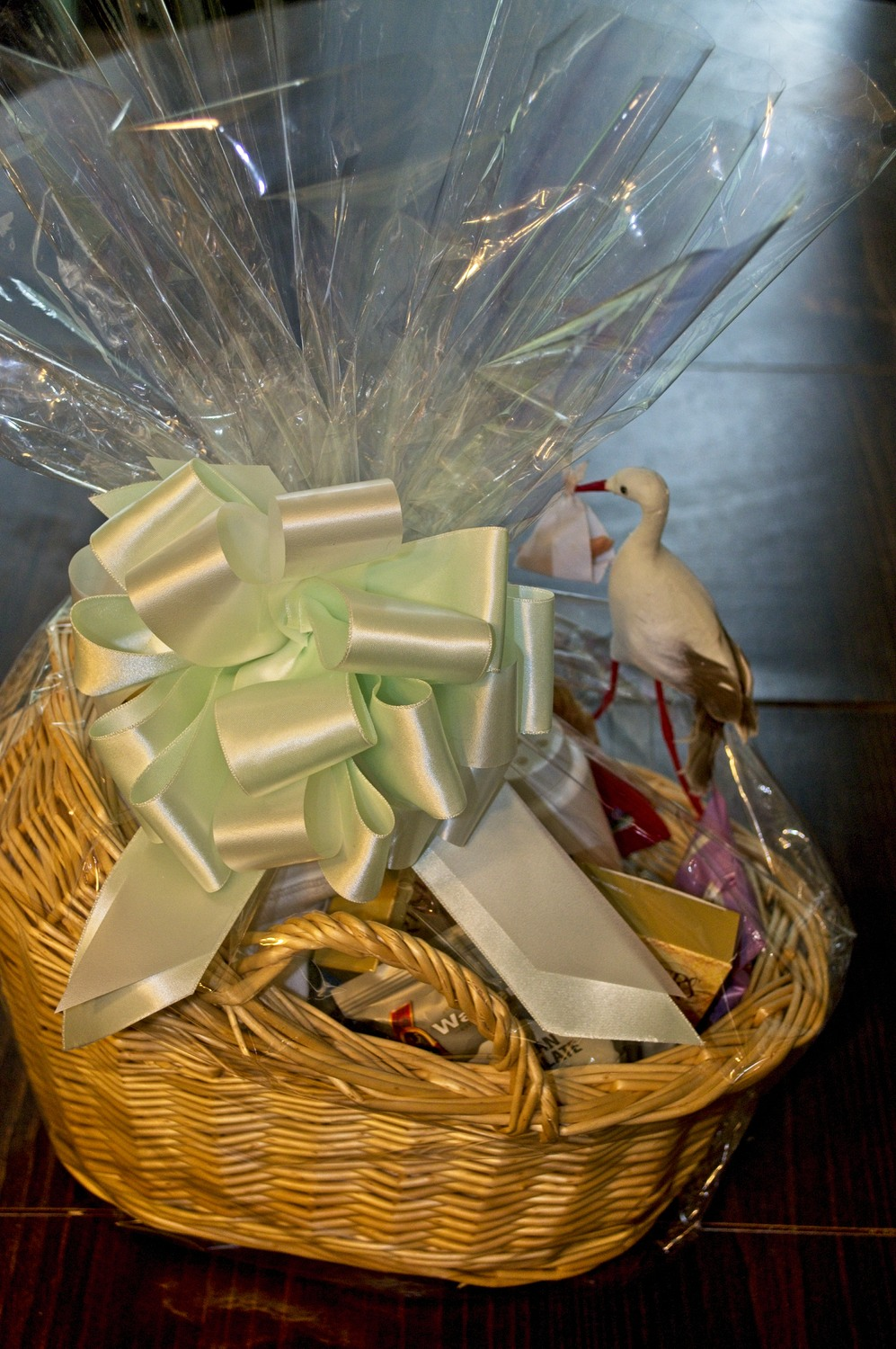 cradle-shaped basket filled with gifts for baby and parents